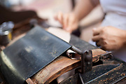 Detail shot of a cigar being made in a hand press. Brazilian Bahian women making cigars in a small factory from fresh tobacco, in the small city town of Cahoeira in Bahia, Brazil, which is know for it's quality tobacco.