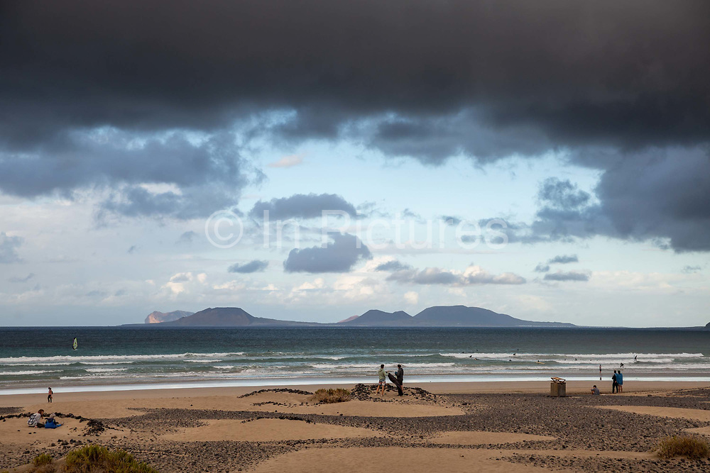 Surfers and walkers enjoy the fresh air as rain clouds roll in from the Atlantic Ocean on 25th November 2020, over Famara Beach, with La Graciosa island in the distance, in Lanzarote, Spain. Rain is actually very rare, with an average of only 16 days of rainfall annually, usually between December and February. The Canary Islands have warm and sunny weather all year round, with temperatures rarely under 16ºC 61ºF in winter and 25ºC 77ºF in summer. .