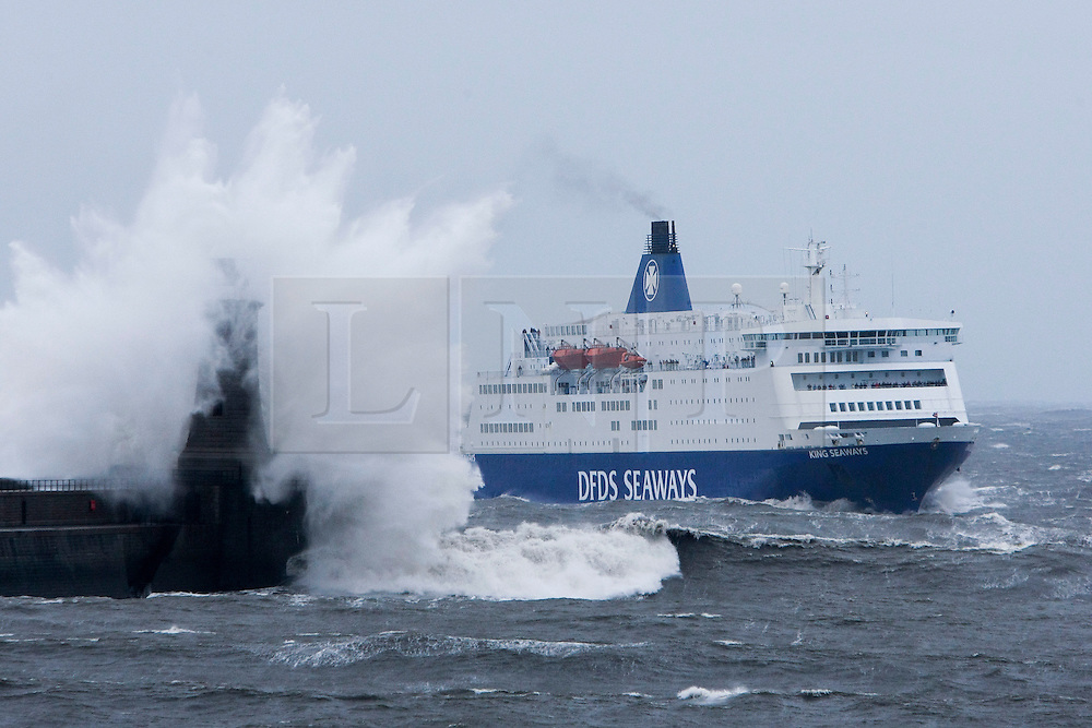 © Licensed to London News Pictures. 26/03/2013. A DFDS Seaways Ferry returning from Amsterdam, passing waves crashing against a lighthouse off the coast of Tynemouth, North East England. British tourists who booked a weekend 'mini-cruise' to Amsterdam spent just six minutes in the Dutch capital after their overnight ferry crossing turned into a 30-hour journey from hell. Photo credit : John Millard/LNP
