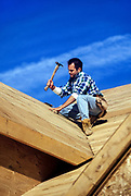 Construction worker on roof of new house construction.