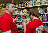 """Officer Eric Adams and Nolan Benoit add warning stickers to alcoholic beverages at Vista Foods as part of the """"Sticker Shock"""" program with Stand Up Laconia and the Laconia Middle School 8th grade class.  (Karen Bobotas/for the Laconia Daily Sun)"""