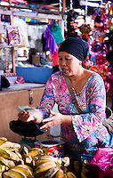 Woman vendor hands back some change after a sale.