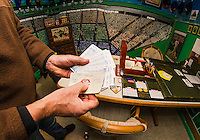 """Bill Colby pulls out the 1971 Baseball season his group is playing with the Strat-O-Matic game in his """"Fenway Park"""" room.  (Karen Bobotas/for the Laconia Daily Sun)"""