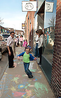 Jayda Glines tip toes through the imagery outside of Frates Creative Arts Center after Jayda and her fellow art students decorated the sidewalk with their chalk creations.  (Karen Bobotas/for the Laconia Daily Sun)