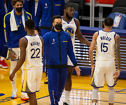 Mar 26, 2021; San Francisco, California, USA; Golden State Warriors guard Stephen Curry, center, in blue sweatsuit, greets his teammates during a timeout in the fourth quarter of an NBA basketball game against the Atlanta Hawks at Chase Center. Curry has sat out the past four games with a bruised tailbone. Mandatory Credit: D. Ross Cameron-USA TODAY Sports