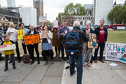 London, UK. 3 May, 2019. A passerby applauds students taking part in the Global Strike for the Future in solidarity with the Fridays for Future climate strikes to call for urgent action against climate change by the British government.
