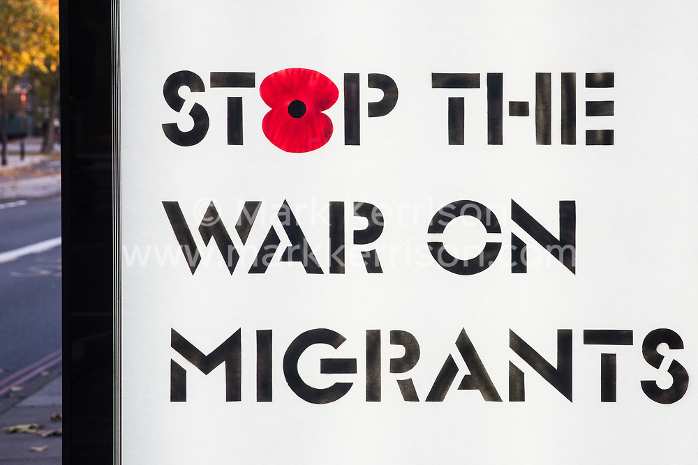 London, UK. 10 November, 2019. Remembrance Sunday artwork by Protest Stencil is displayed at a bus shelter outside the Imperial War Museum. The artwork contains the text 'Stop The War on Migrants', features a red poppy, references the government's hostile environment policies and calls for reflection on Britain's colonial past and present.