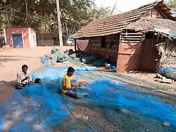 Men sitting mending fishing nets, Chapora, Goa.