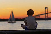 USA, Newport, RI - Sitting alone, a boy watches the sun set behine a yacht on Narragansett bay.