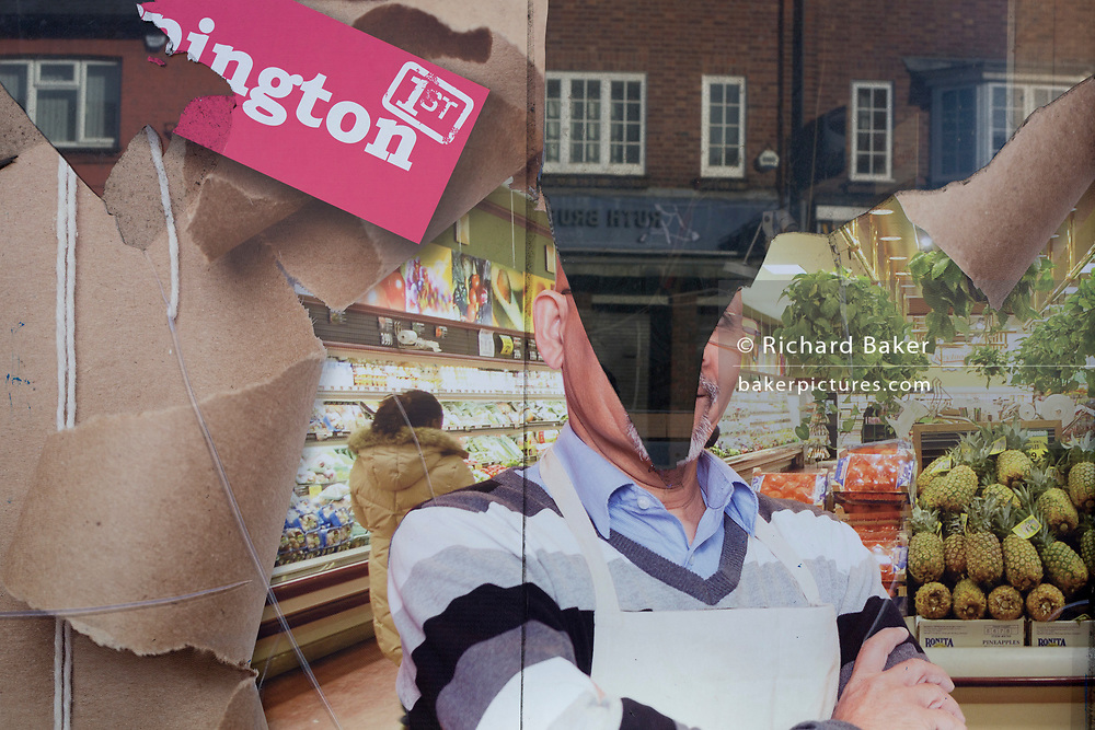 A detail of a torn shop poster showing a supermarket manager, in the window of a business in Orpington High Street, on 5th February 2020, in London, England.