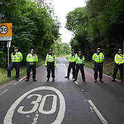 Police block the way to Balcombe next to Balcombe train station where about 40 activists have come off the train to join the 'Reclaim the Power' camp.  The camp is set up in a field in solidarity with the local movement already in swing to stop the gas fracking company Cuadrilla from operating.
