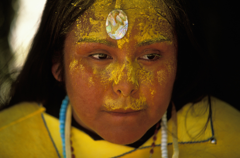 After six hours of continuous dancing at a Sunrise Dance, an Apache girl's first menstruation rite, the girl rests in camp on the San Carlos Apache Indian Reservation in Arizona, USA. The girl is covered with sacred yellow pollen from the cattail plant, which has been applied as a blessing by the medicine man and the relatives. The Sunrise Dance is an enactment of the Apache creation myth and during the rites the girl 'becomes' Changing Woman, a mythical female figure, and comes into possession of her healing powers. The rites are also supposed to prepare the girl for adulthood and to give her a long and healthy life without material wants.