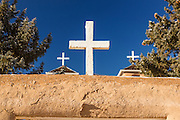 A white cross on the historic San Francisco de Asis Mission Church in Ranchos de Taos Plaza, Taos, New Mexico. The adobe church built in 1772 and made famous in paintings by artist Georgia O'Keeffe.
