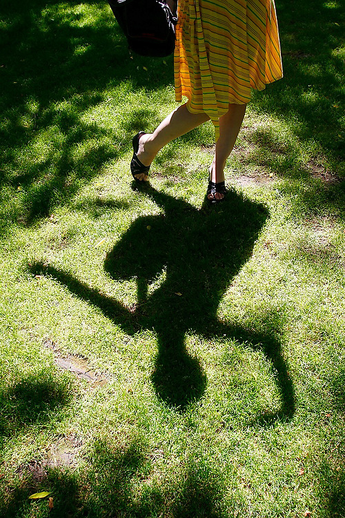 A young woman's shadow is projected onto the grass lawn at her feet on the University of Washington campus in Seattle, Washington.