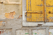 Peeled paint with yellow door in Syros, Greece