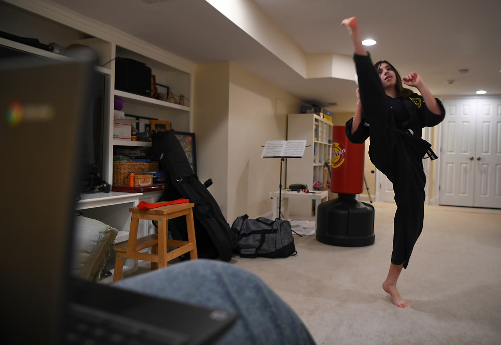4/21/20 4:54:45 PM -- Maddie Gruber, 11, earned her first degree blackbelt in 2020 has Zoom workouts and instruction with Jhoon Rhee Tae Kwon Do in the family basement during the Covid-19 pandemic as all non-essential business is shut down in Virginia.  The Gruber family under stay at home restrictions in Virginia and Fairfax County Schools cancelled for the school 2020 school year.  --    Photo by Jack Gruber, USA TODAY Staff