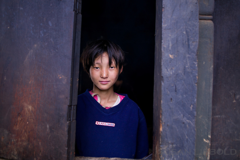 A girl looking out of a window in Bhutan.