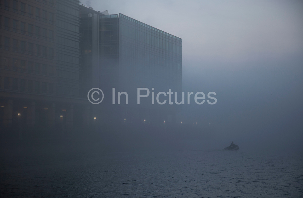 Thick fog over London at the financial district at Canary Wharf making a peaceful yet eerie landscape atmosphere over the waters of West India Millwall Docks  as towers appear and disappear. Modern commercial architecture is releaved through a mist which lasted tthrough the entire day.