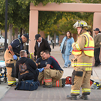 Firefighters and EMTs work together to stabilize and transport a woman involved in a hit an run in the pedestrian cross walk on Aztec near Second Street in Gallup Friday.
