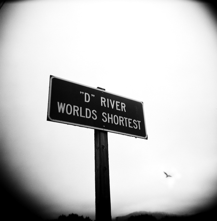 """Though the D River's honor of """"world's shortest river"""" was challenged in 1987 by a group of ornery schoolchildren in Great Falls, Mont., the celebratory signs along Highway 101 in Lincoln City remain...""""It's 105 feet, give or take five feet,"""" said Jill Elfstrom, longtime employee of Kyllo's Seafood Grill, the restaurant that sits along side the river for most of its length. """"Devil's Lake is a spring-fed lake, so [the body of water that connects it to the Pacific Ocean] fits all the criteria of being a river. I'm an old-time Lincoln City resident, and we like our information correct.""""..On the beach, Jody McDonald of Salem showed the river to friends visiting from Texas, including Melissa White, who grew up in Portland...""""Growing up, we used to go to Cannon Beach, but that's gotten kind of boring,"""" White said. """"But I can't go home without coming to the beach.""""..""""Don't get wet!"""" one of her friends exclaimed, as she stepped into the slow, shallow, legendary D River...""""That's part of going to the beach,"""" White responded."""
