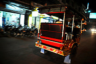 Rear view of tuk tuk driving at night in a street of Phnom Penh, Cambodia, Southeast Asia