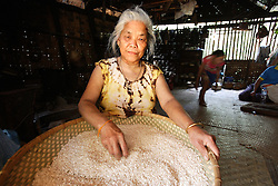 Chan Souk, 67 is a member of the Older People's Group. She is cleaning the small stones and husk from sticky rice, the staple food, before cooking it.<br /> Had Khen Village, Pakseng District, Luang Prabang Province, Lao PDR