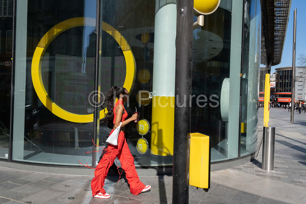 The yellow theme shapes and window design of confectionary retailer M&Ms, with a young woman in red, during the third lockdown of the Coronavirus pandemic, on 29th March 2021, in London, England.