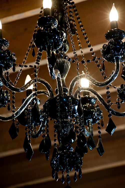 Black chandelier with lights on and black and crystal beads at Peche's Resturant and Bar.