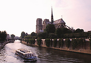 Rear view of the Notre Dame Cathedral with a boat in the foreground on the river Seine, Paris