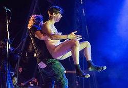 © Licensed to London News Pictures.  02/09/2017; Bristol, UK. WARNING, NUDITY: Picture of security trying to restrain a male streaker who invaded the stage as ELBOW with singer Guy Garvey performed at The Downs Festival 2017 on The Downs in Bristol. Guy Garvey then took the streaker's hand and embraces the streaker. Picture credit : Simon Chapman/LNP