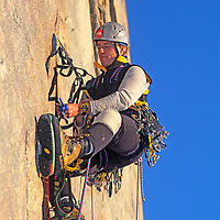 A mountaineer aid climbs high up a big wall on Great Sail Peak, a massive cliff on Baffin Island, Nunavut, Canada.