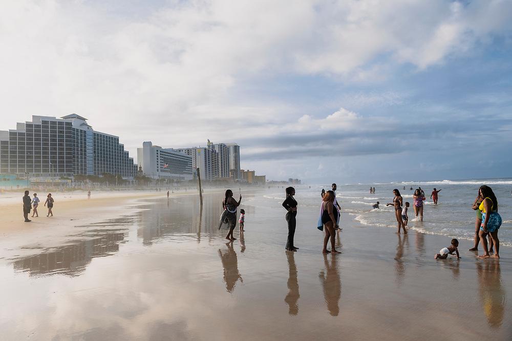 Daytona Beach, Florida - August 26, 2021: People enjoy the beach in Daytona shortly before sunset on a summer day.