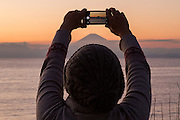 A Japanese woman uses an iphone to take a photo of Mount Fuji during the last sunset of 2016. Muira, Kanagawa, Japan Saturday December 31st 2016