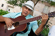 Cuban man plays the guitar and sings, with an intense stare, in the street in Havana old town.