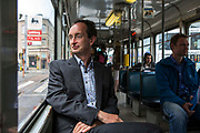 Portrait of Patrick De Boeuf, Chief Executive of De Lijn proudly sits on one of his modern electric tram buses on the Ghent Tramway Network in central Ghent, Belgium.
