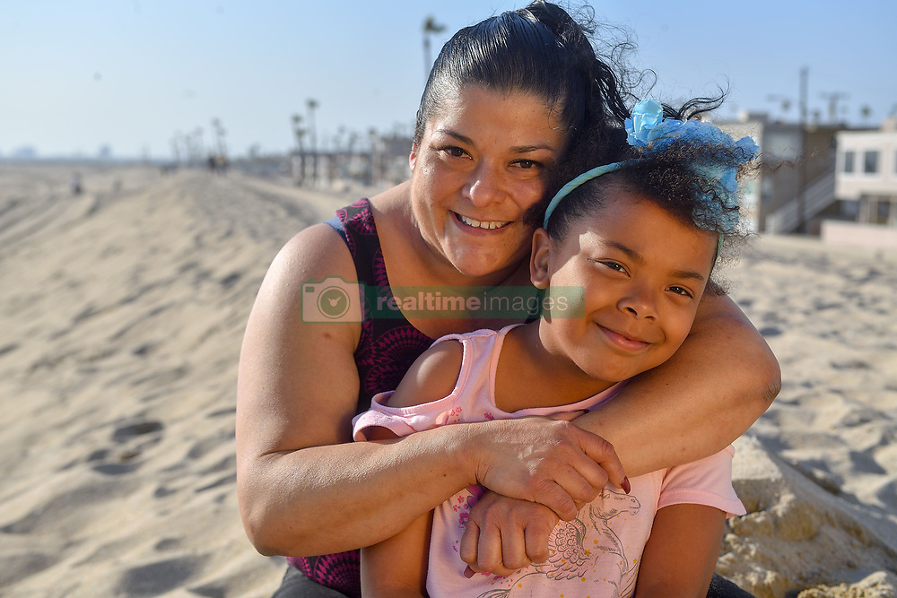 March 25, 2019 - Seal Beach, California, U.S. - Traci Morales and her daughter Elizabeth Levingston, 8, on the sand in Seal Beach, CA, on Monday, March 25, 2019. Levingston was swept out to sea as she and her friends were playing in ankle-deep water. A passerby ran out to rescue her and now Morales is searching for her rescuer to say thanks.  (Photo by Jeff Gritchen, Orange County Register/SCNG)...Levingston was swept out to sea as she and her friends were playing in ankle-deep water. A passerby ran out to rescue her and now Morales is searching for her rescuer to say thanks. (Credit Image: © Jeff Gritchen/SCNG via ZUMA Wire)
