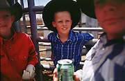 05 AUGUST 2000 - WILLIAMS, AZ: Young cowboys sit above the livestock chutes and wait for the action to begin at the 22nd Annual Cowpunchers' Reunion Rodeo in Williams, Arizona, Aug 5.  The Cowpunchers' Reunion Rodeo is held for working cowboys from the ranches in Arizona and the region. PHOTO BY JACK KURTZ