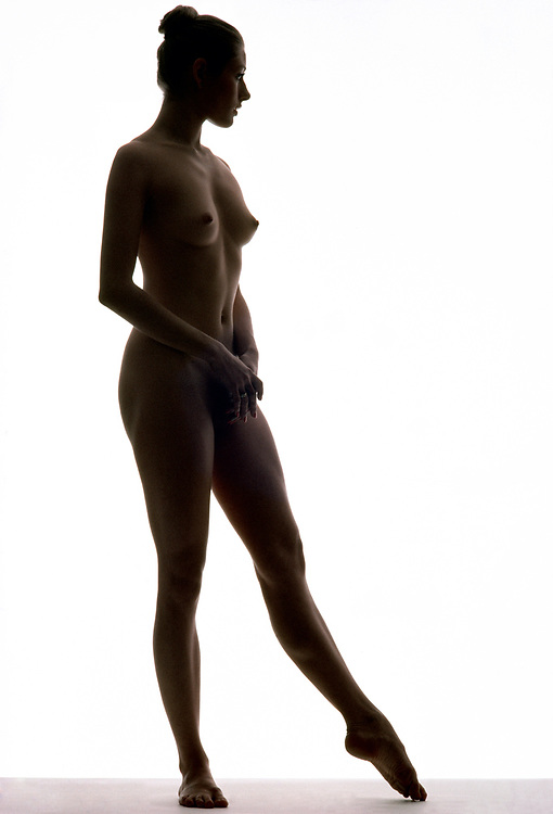 Full length nude woman gracefully posing in silhouette against a white background