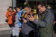 Asian tourists struggle with smartphone technology while outside Selfridges on Oxford Street on a bright day in central London. Concentrating on their screens in the middle of the chaos of this busy shopping street, the visitors to the capital look frustrated and cross with their apps or messaging. One has the look of an angry consumer of electronics - possibly about to throw his handset across the road. Others walk past unaware of the reaction, preferring instead to pass-by.