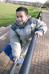 Little boy playing on park railings,