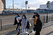 With local coronavirus lockdown measures in place and Birmingham currently set at 'Tier 2' or 'high', a group of youths wearing face masks walk past the empty area of the wholesale markets precinct, which is partially used as a parking lot in the city centre on 26th October 2020 in Birmingham, United Kingdom. The three tier system in the UK has levels: 'medium', which includes the rule of six, 'high', which will cover most areas under current restrictions; and 'very high' for those areas with particularly high case numbers. Meanwhile there have been calls by politicians for a 'circuit breaker' complete lockdown to be announced to help the growing spread of the Covid-19 virus.