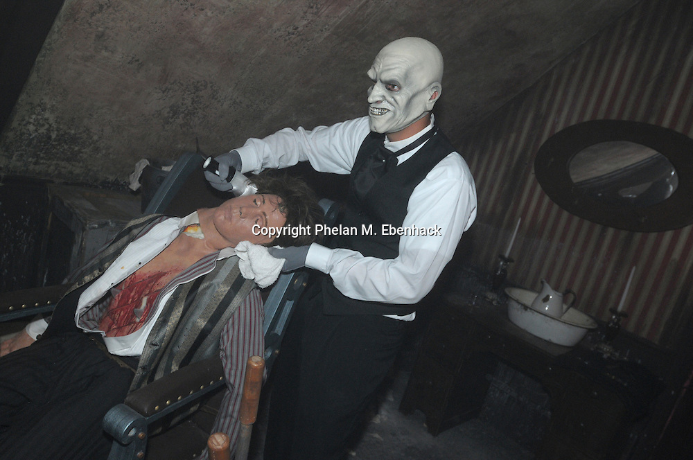 A ghoul posing as a barber prepares to shave a dead man in the Body Collectors: Collections of the Past venue during a dress rehearsal of Universal Studios Florida's Halloween Horror Nights in Orlando, Fla., Tuesday, Sept. 16, 2008.
