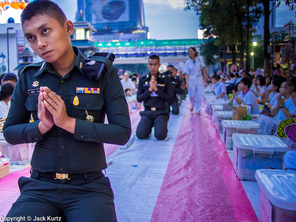 08 SEPTEMBER 2013 - BANGKOK, THAILAND: Police officers pray during a mass alms giving ceremony in Bangkok Sunday. 10,000 Buddhist monks participated in a mass alms giving ceremony on Rajadamri Road in front of Central World shopping mall in Bangkok. The alms giving was to benefit disaster victims in Thailand and assist Buddhist temples in the insurgency wracked southern provinces of Thailand.      PHOTO BY JACK KURTZ