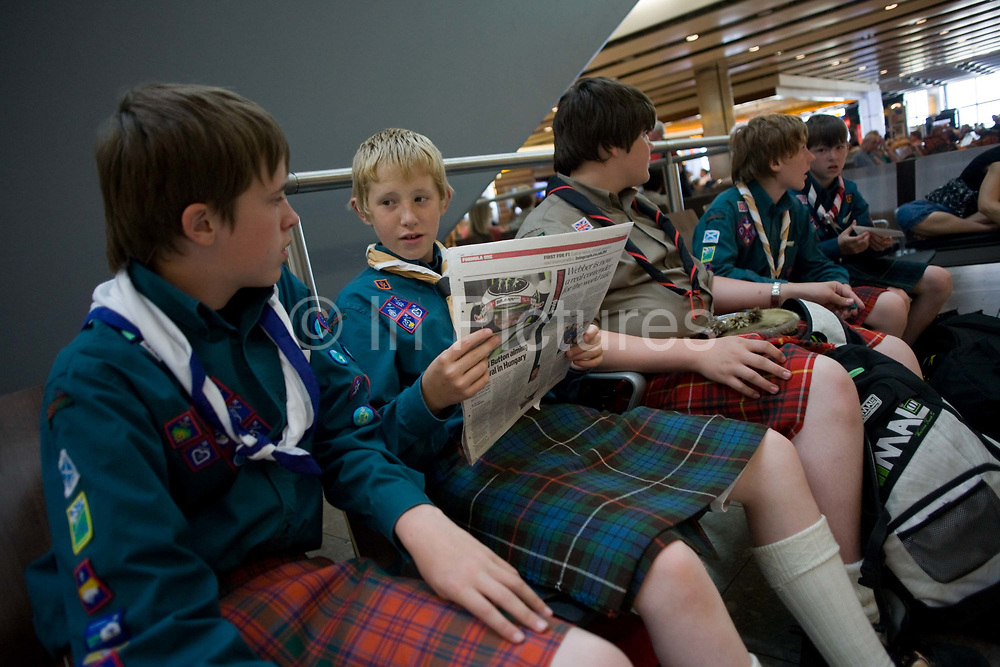 """Boys from a Scottish scout group sit and in the departures concourse of Heathrow Airport's Terminal 5. All wearing traditional kilts favoured by the Scots, the lads are en-route between Switzerland and Scotland after a week's international jamboree in the Alps. Their sleeves are filled with the stitched badges of past achievements and one reads a newspaper while the others pass away the time before their flight by watching other passengers. The kilt's are alternately red and green and historically, relate to their wearers old family clans. From writer Alain de Botton's book project """"A Week at the Airport: A Heathrow Diary"""" (2009)."""