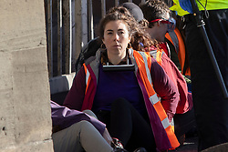 © Licensed to London News Pictures. 03/10/2021. London, UK. An activist from Insulate Britain with a bike lock around her neck blocks the entrance to the Blackwall tunnel. Insulate Britain have successfully blocked various roads around the capital over a number of weeks, resulting in a court injunction banning them from going near the M25 motorway.  Photo credit: George Cracknell Wright/LNP