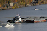 Fort Montgomery, NY - A tugboat pushes barges down the Hudson River just south of the Bear Mountain Bridge as motorboats head up and down the river in the foreground and background on Nov. 2, 2008.