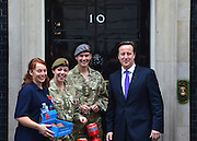 © Licensed to London News Pictures. 25/10/2012. Westminster, UK (L_R) Ali Baserville, photojournalist. Captain French, Captain Crossley, David Cameron. British Prime Minister David Cameron buys a poppy from soldiers on the doorstep of Number 10 Downing Street today at the start of the Royal British Legion's 2012 poppy appeal. Photo credit : Stephen Simpson/LNP