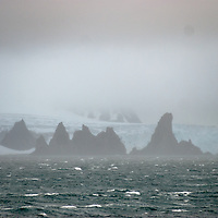 Fog shrouds rock spires, a glacier and mountains in the South Shetland Islands, north of the Antarctic Peninsula, Antarctica.