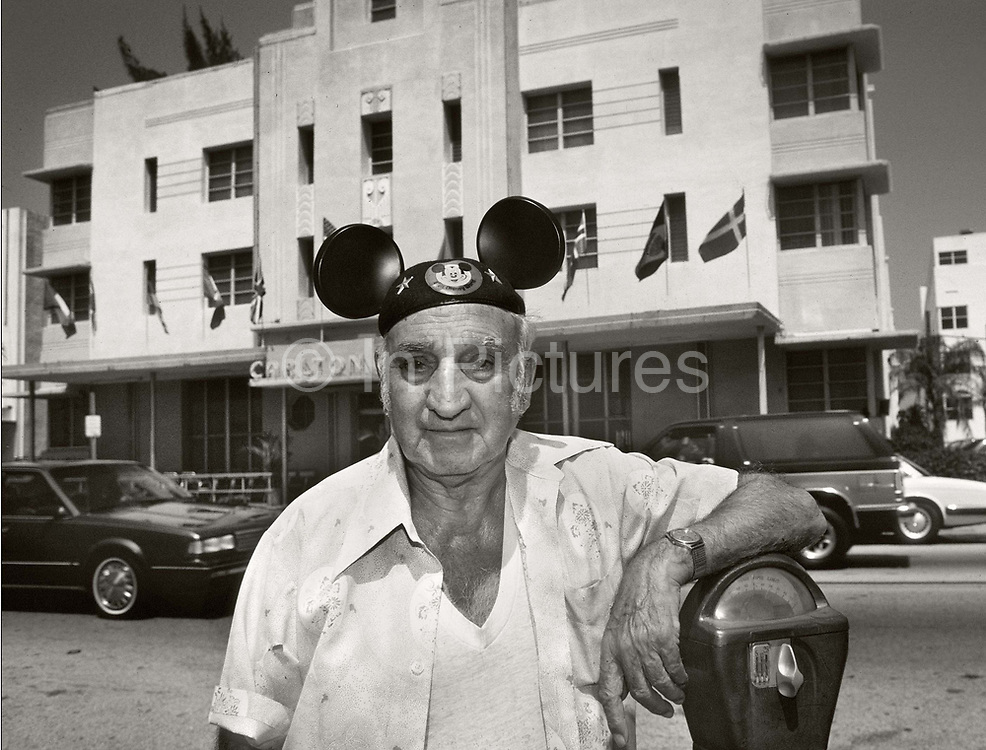 Elderly man standing by a parking meter in front of the Carlton Hotel, Washington Avenue, Miami Beach, wearing a Micky Mouse hat.