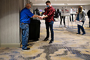 03 NOVEMBER 2020 - WEST DES MOINES, IOWA: An election worker gives hand sanitizer to a voter who dropped off his ballot at the West Des Moines Marriott on Election Day in West Des Moines. Voter turnout was heavy at most polling places in the Des Moines metro area.      PHOTO BY JACK KURTZ